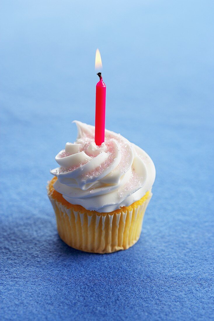 A Yellow Cupcake with Vanilla Frosting and a Lit Red Candle