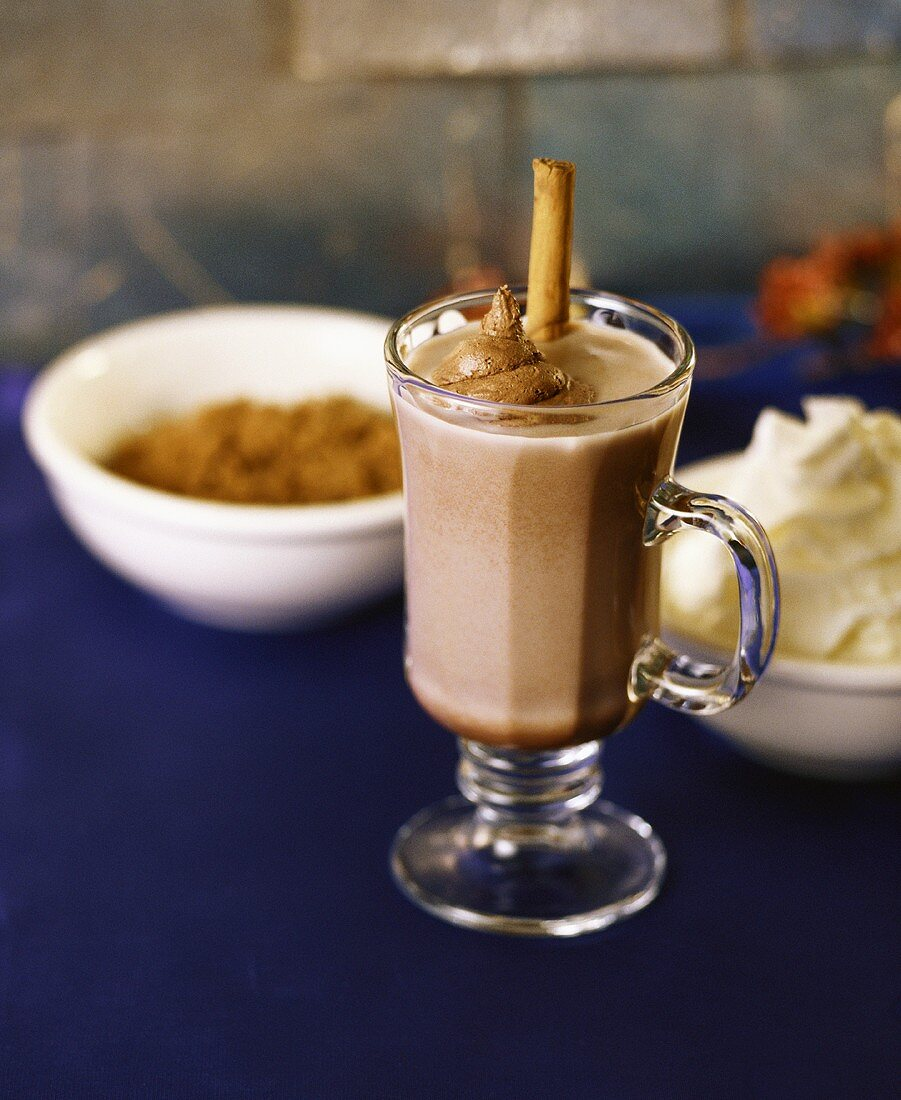 Hot chocolate with chocolate whipped cream and cinnamon stick