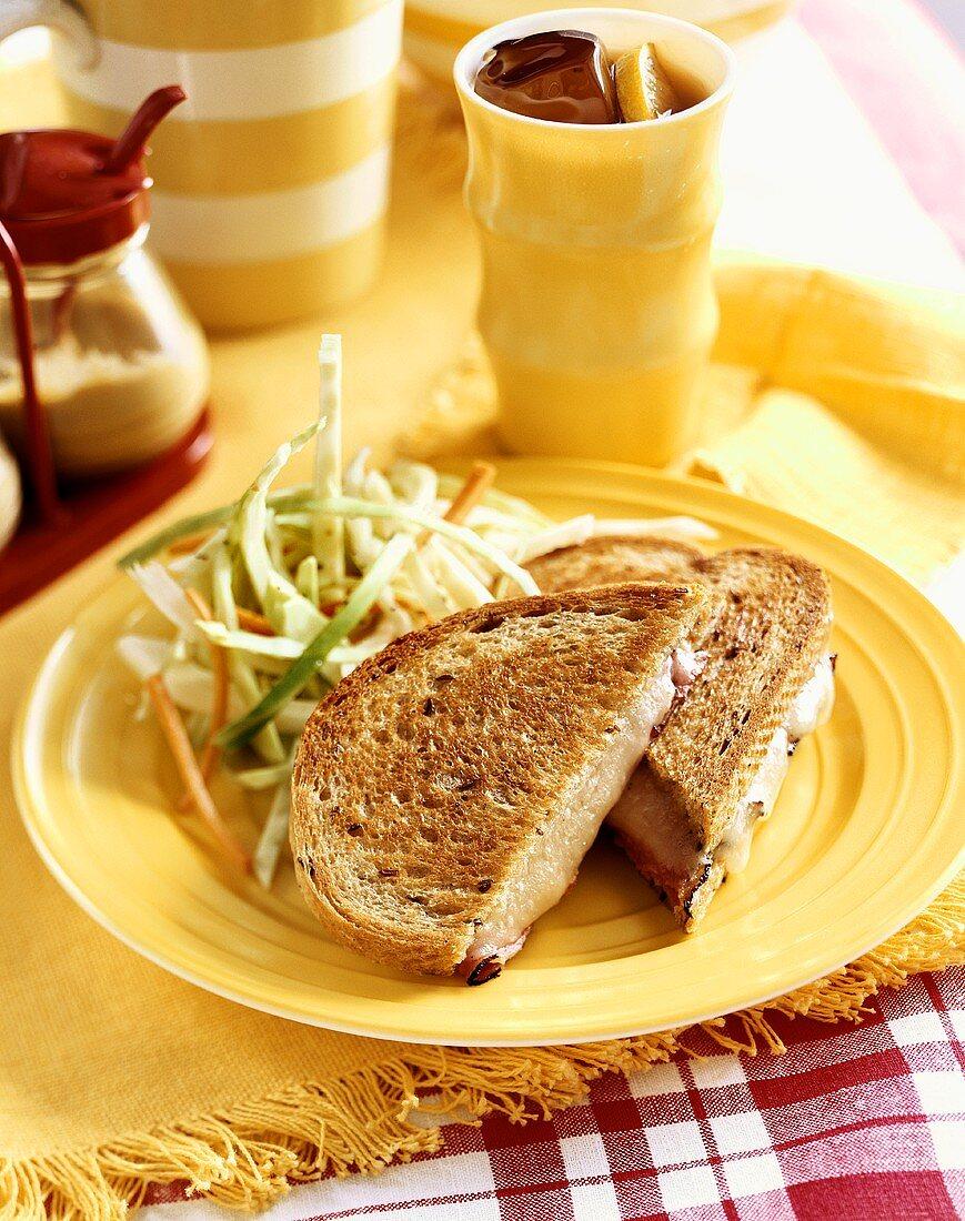 Ruben Sandwich Cut in Half with a Side of Slaw; Glass of Iced Tea