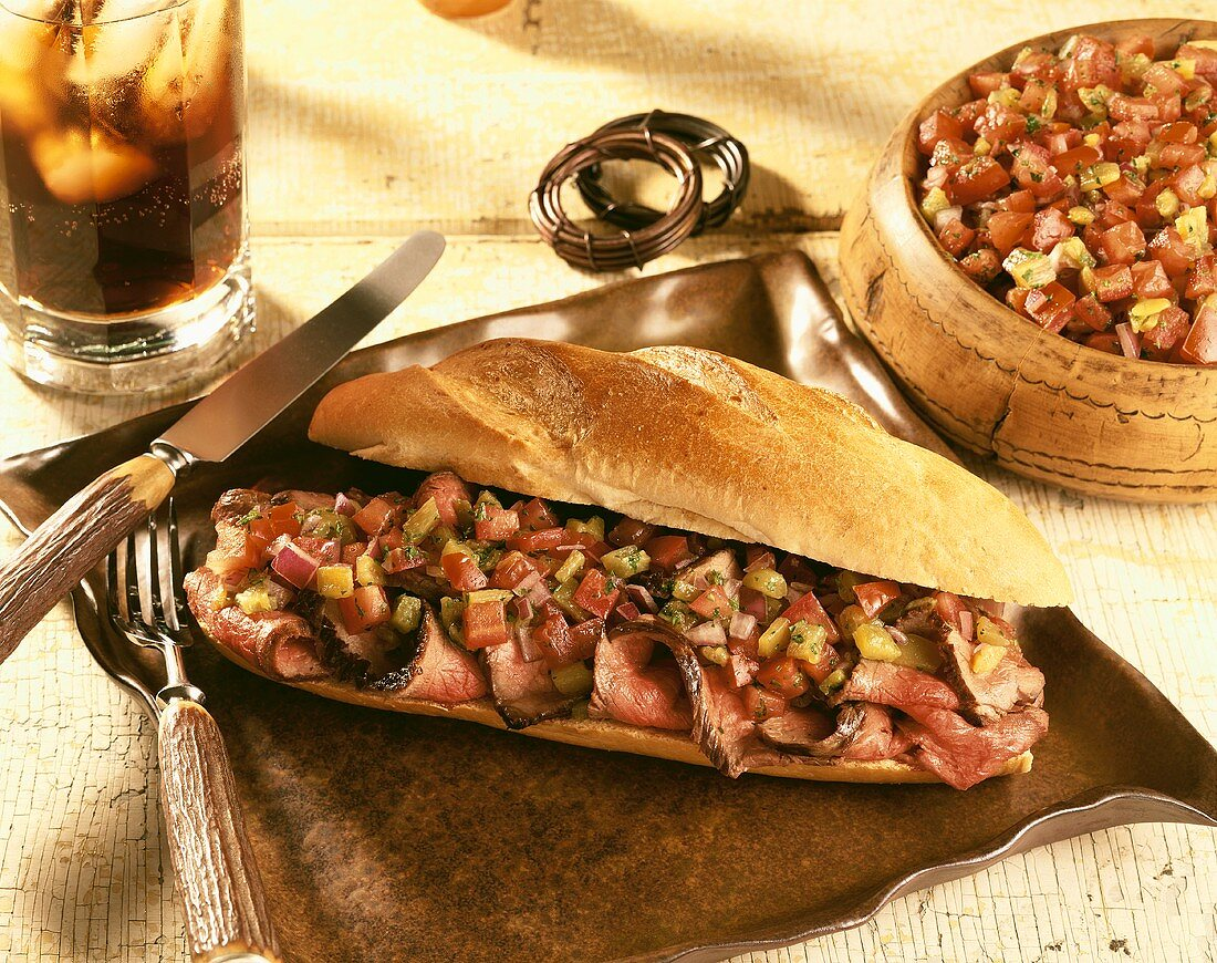 Steak Sandwich Topped with Onions, Tomatoes and Peppers on Crusty Sub Roll; Salsa