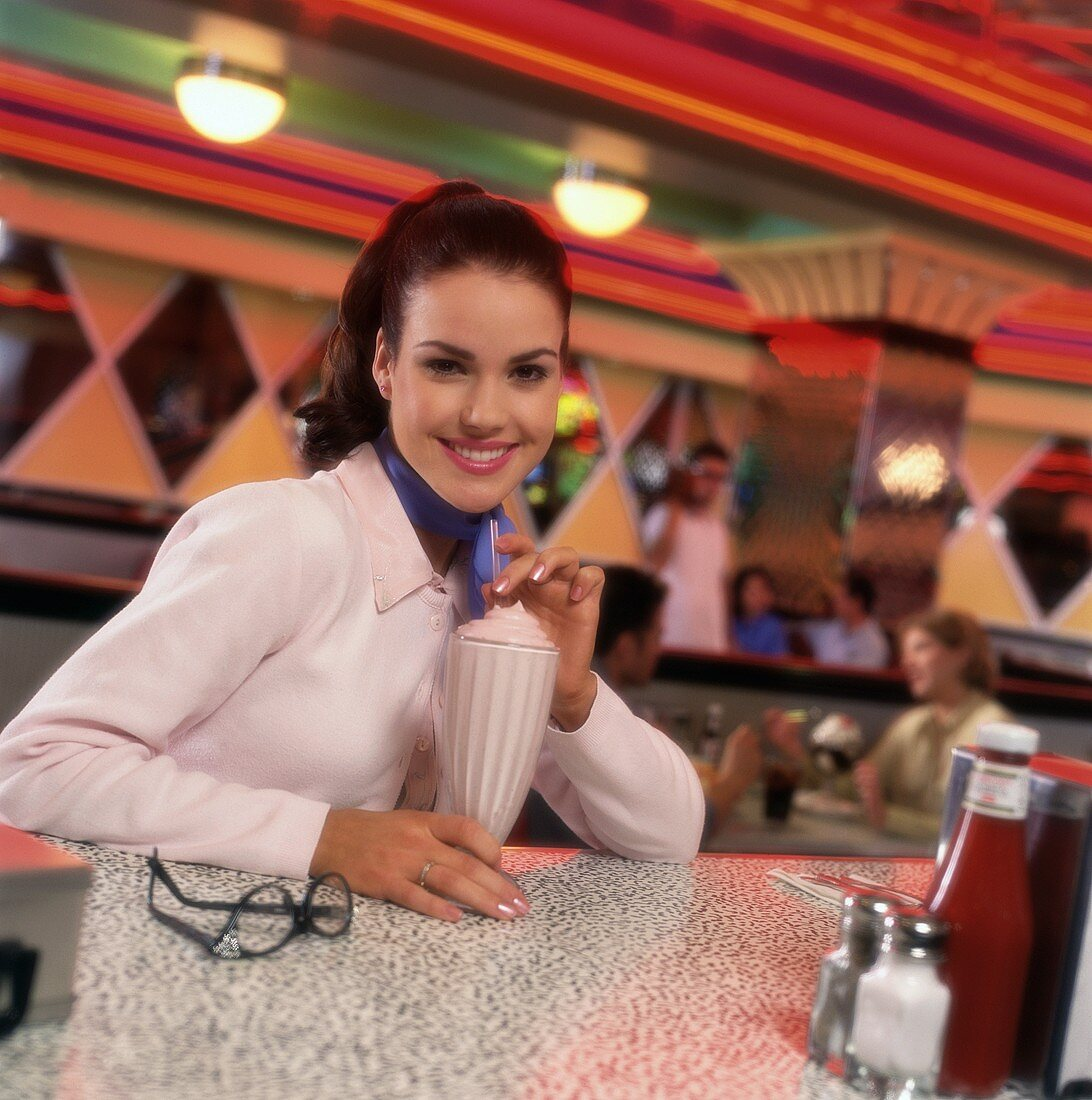 Young woman with milkshake in a snack bar