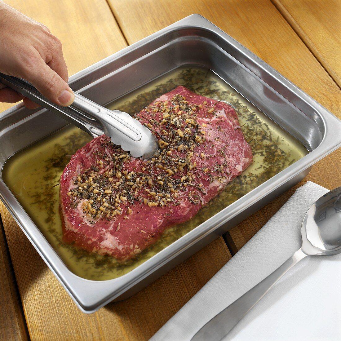 Turning steak in herb marinade
