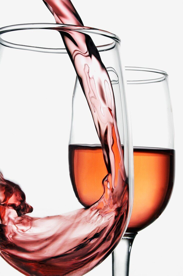 Blush Wine Pouring into Wine Glass; Half Full Glass of Wine