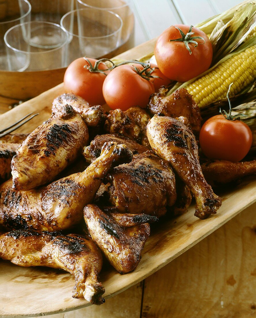 Grilled chicken pieces with tomatoes & corncobs on platter