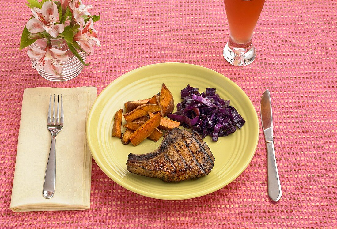 Place Setting with Grilled Pork Chop Served with Sweet Potato Fries and Red Cabbage
