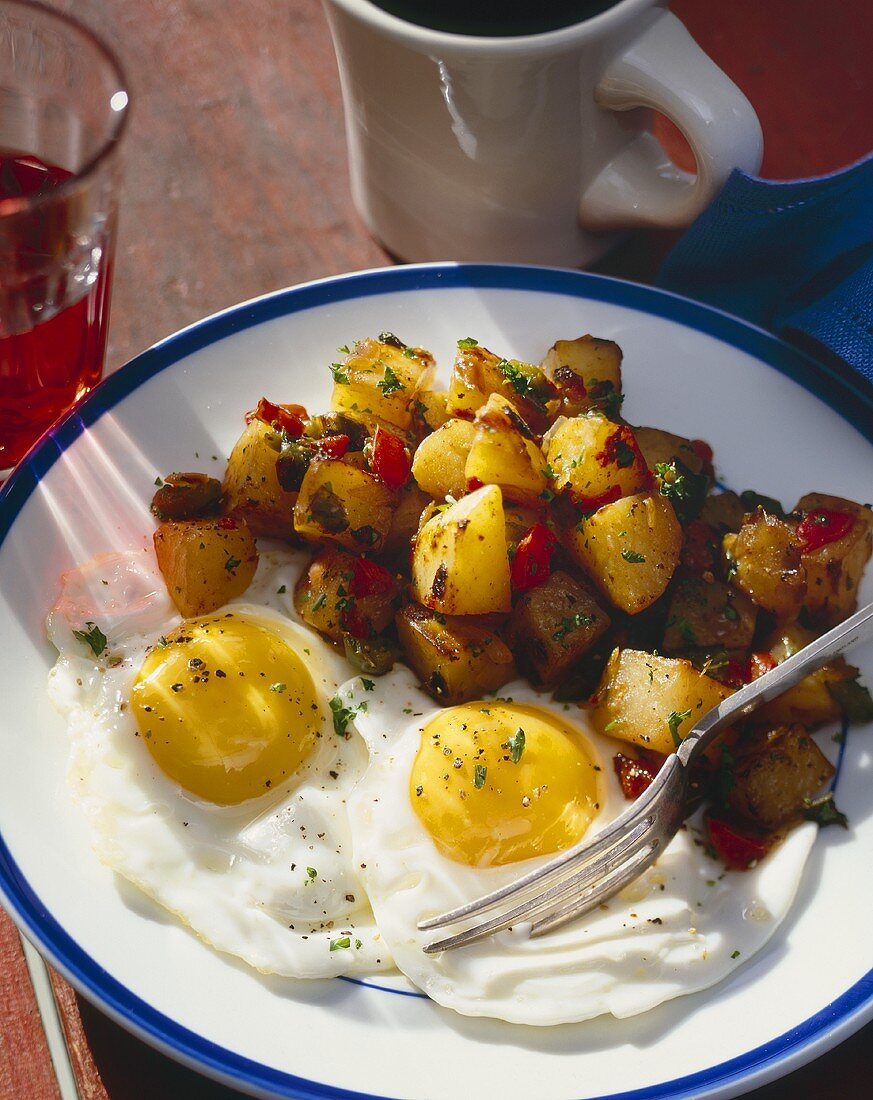 Two Eggs Sunny Side Up with Hash Brown Potatoes on a Plate with a Fork; Cup of Juice and Coffee