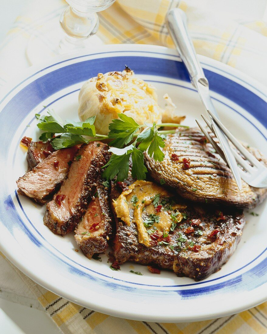Partially Sliced Grilled Steak with a Grilled Portobello Mushroom and Garlic Bulb on Blue Rimmed Plate