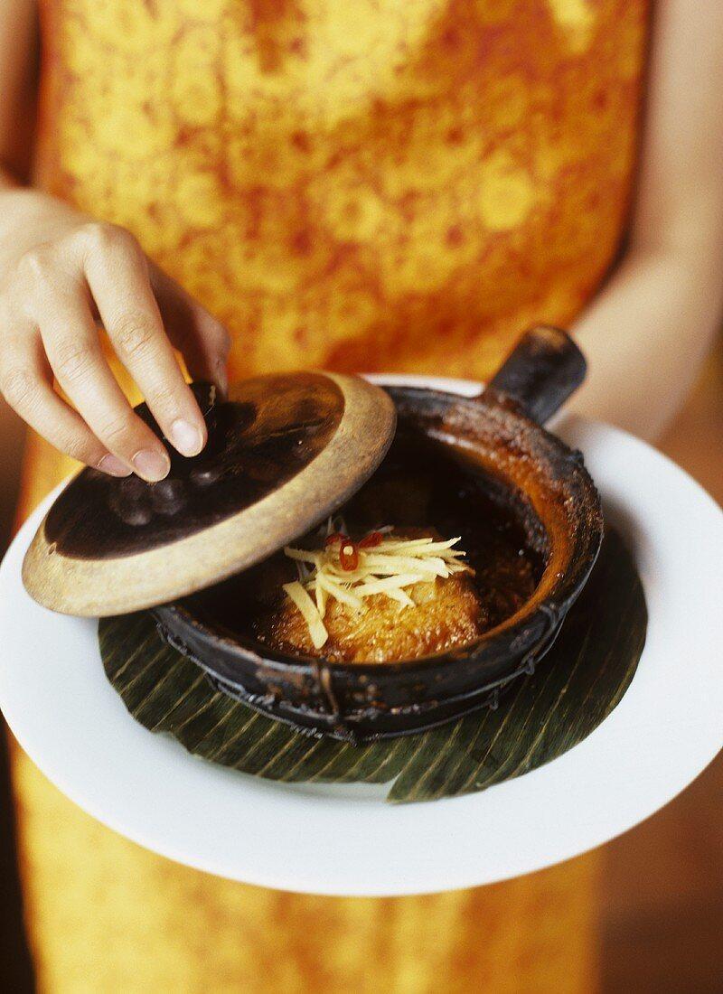 Woman Holding Pot au Feu with Sweet Chili Fish