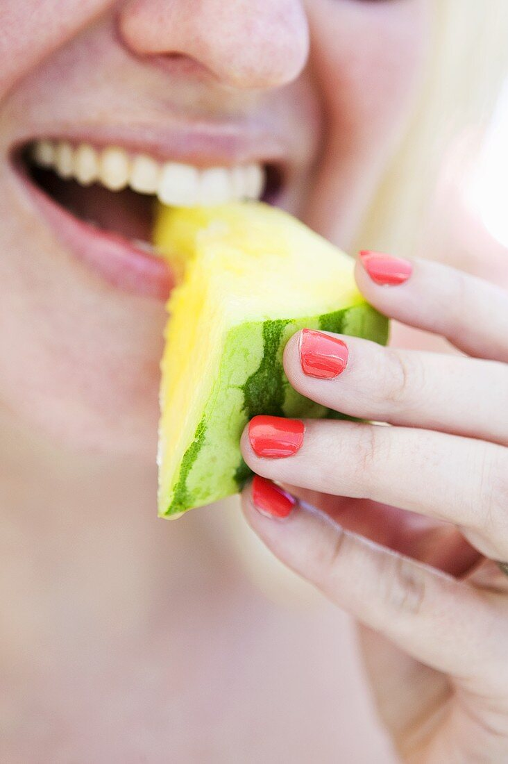 A woman eating a yellow watermelon