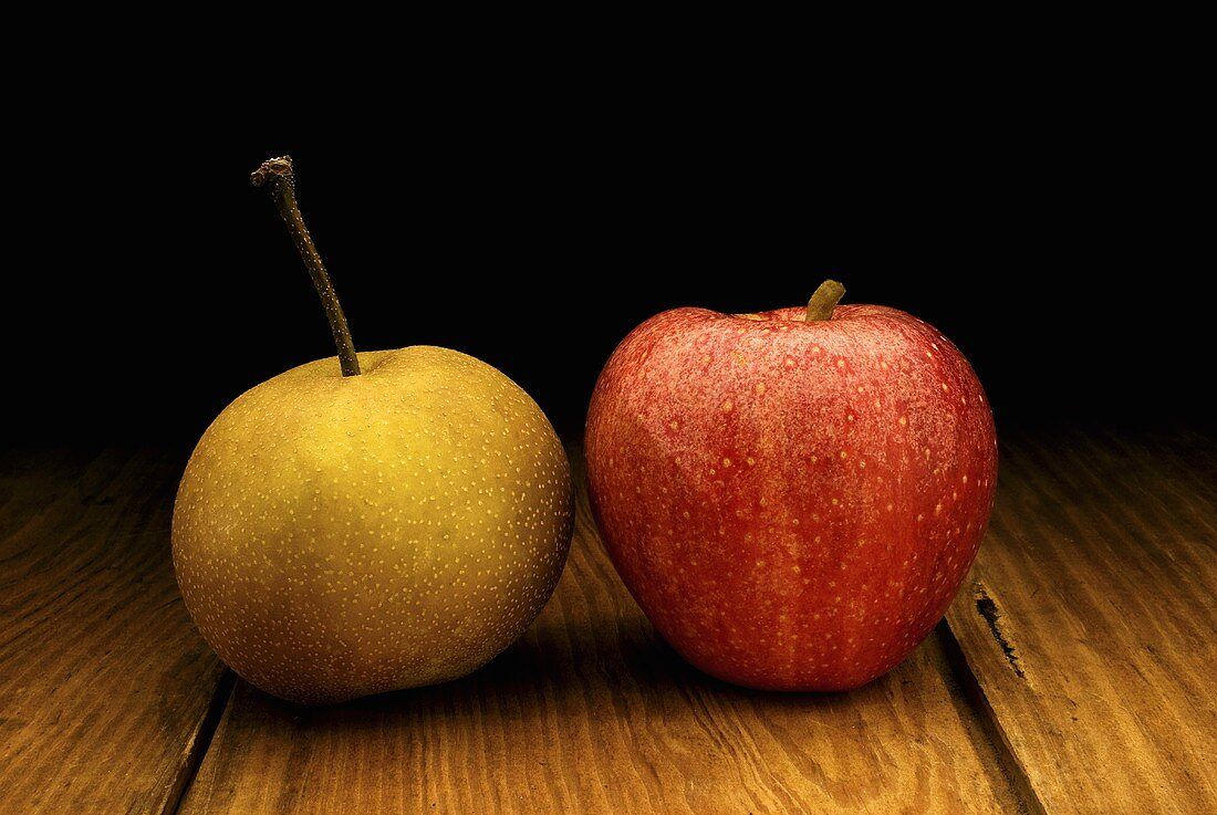 An Asian Pear and Red Apple on a Wood Table