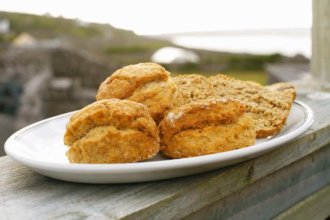 Platter of Scones and Bread on Outdoor Railing Overlooking Stone Fences and Ocean; Aran Island, Ireland
