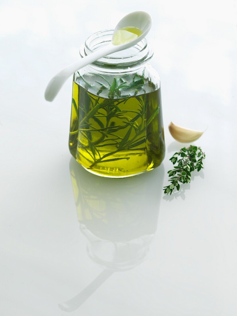 Small Jar of Herb Infused Oil; Fresh Herbs and Garlic; Spoon
