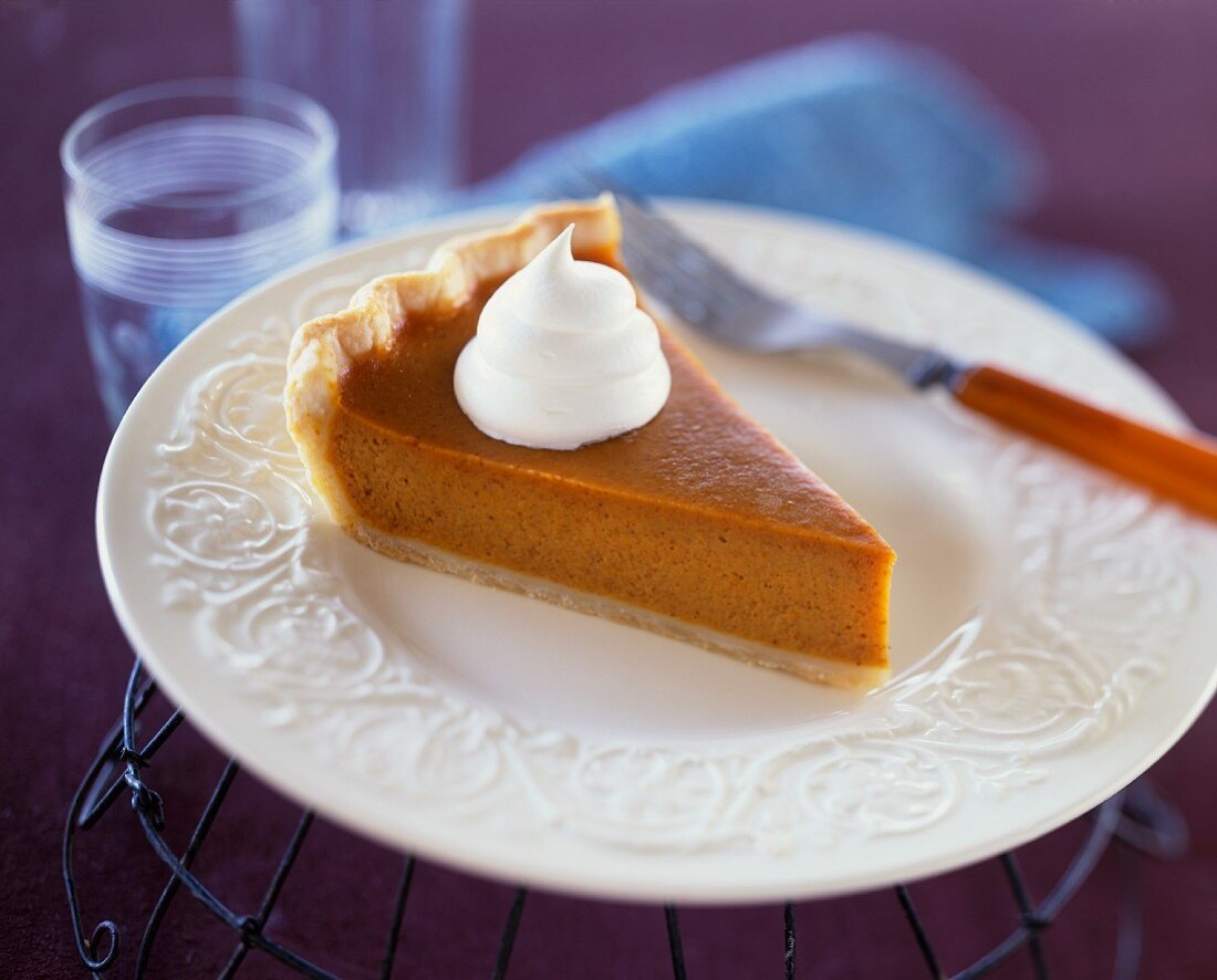 Slice of Pumpkin Pie with a Dollop of Whipped Cream on a White Plate