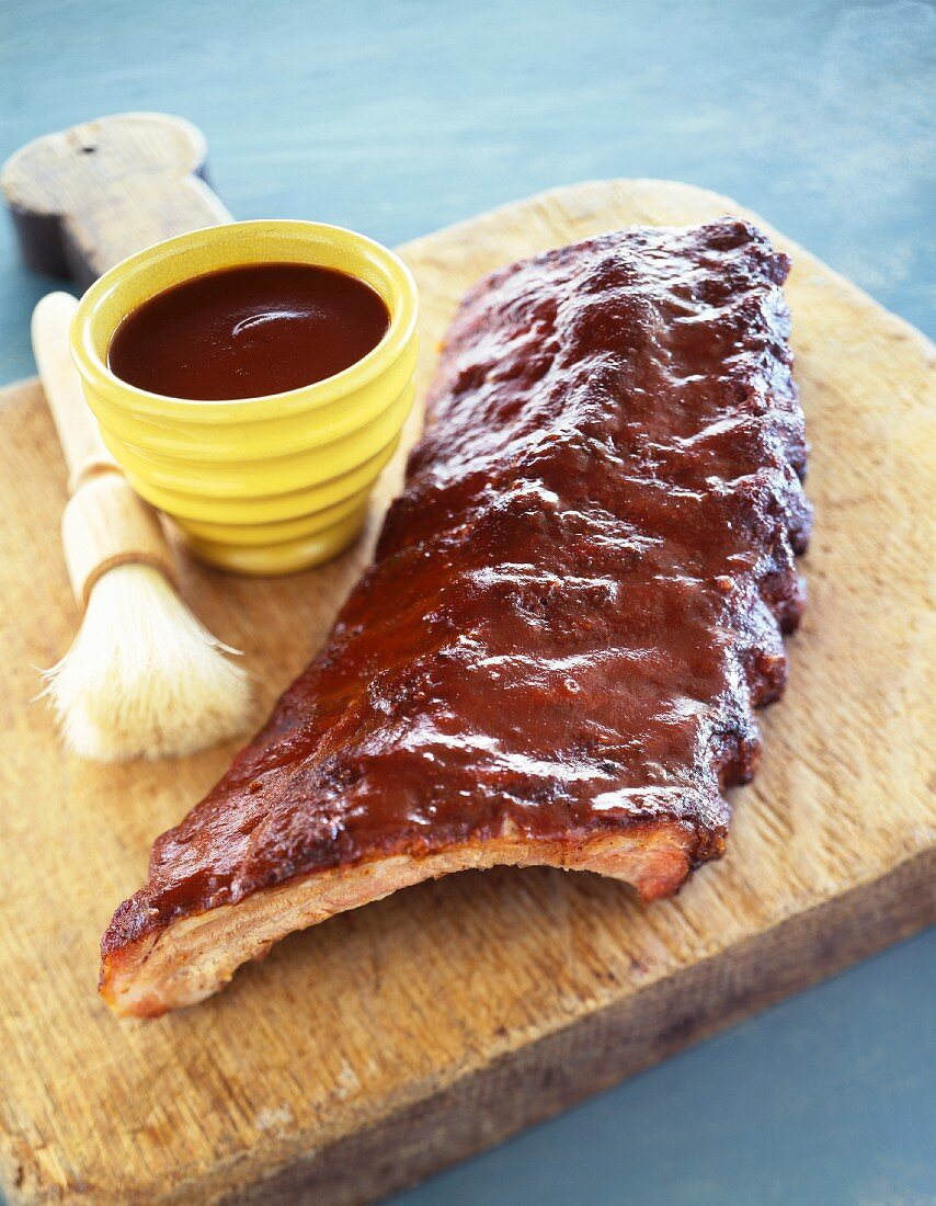 Slab of Barbecue Ribs on a Cutting Board with a Bowl of Sauce and Basting Brush