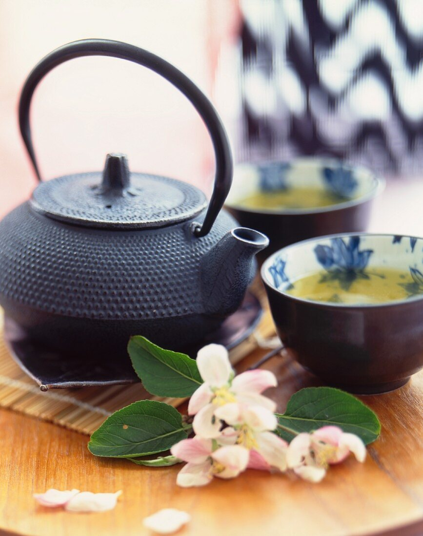 Asian Style Tea Pot and Tea Cups with Fresh Flowers