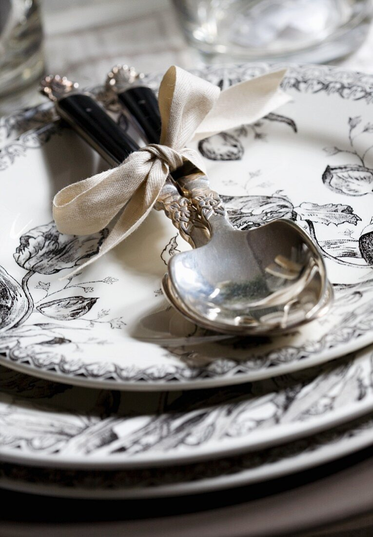 A stack of plates with silver cutlery