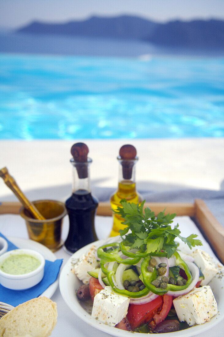 Greek salad on tray by swimming pool, Santorini