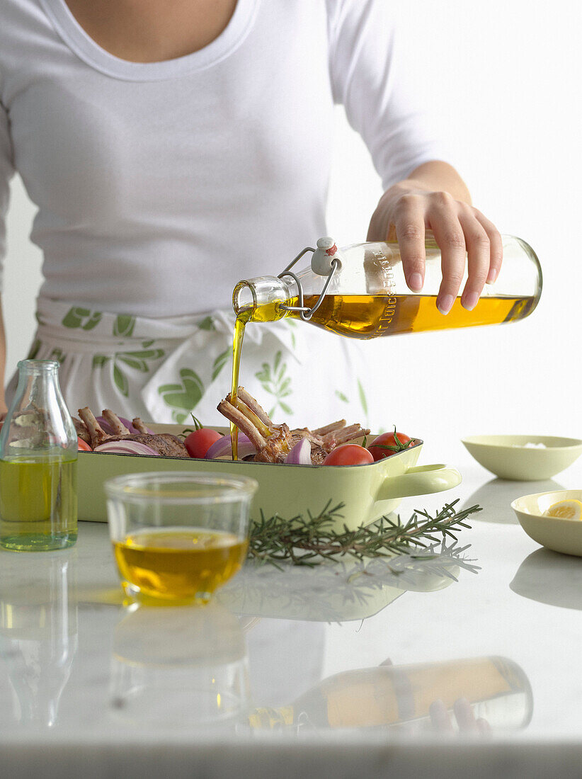 Woman pouring olive oil over roast dish. AAOilGuideOpener