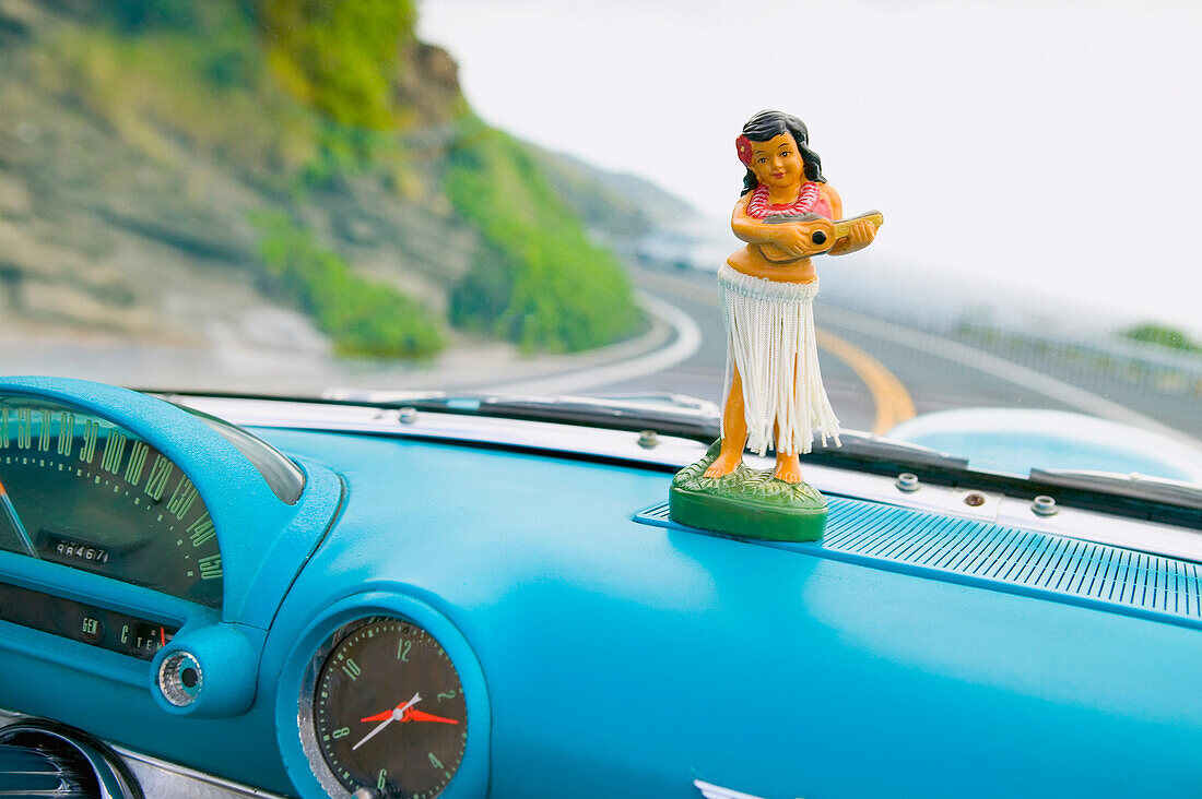 Plastic hula doll on the dashboard of a turquoise Thunderbird.