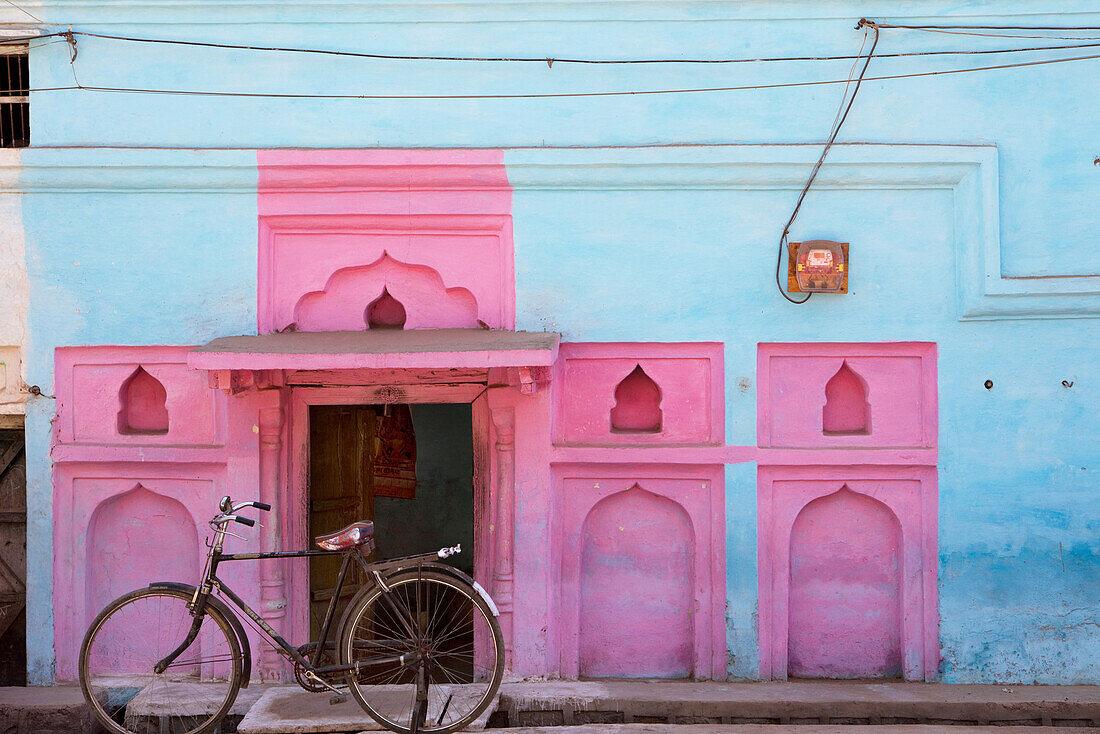 Old bike in front of colorful facade, Khajuraho, Madhya Pradesh, India