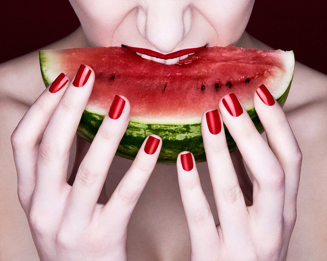 Woman biting slice of watermelon