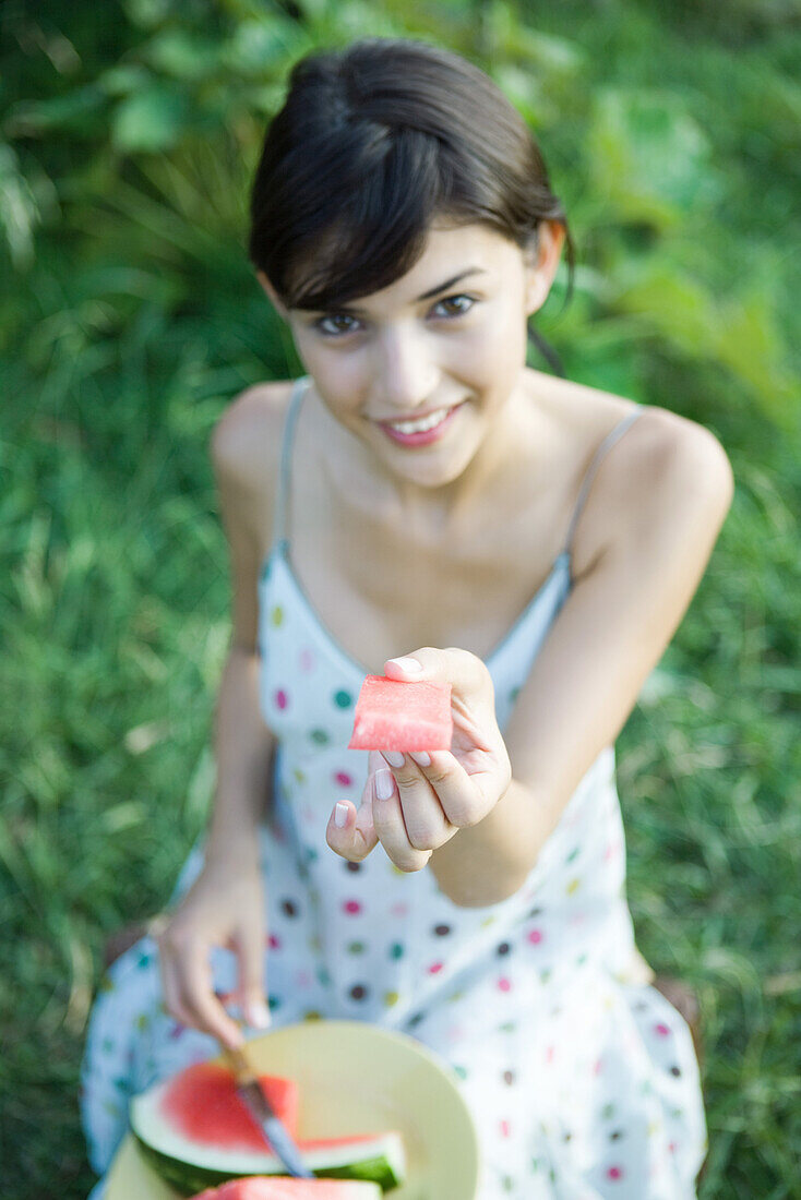 Young woman holding up piece of watermelon, smiling at camera