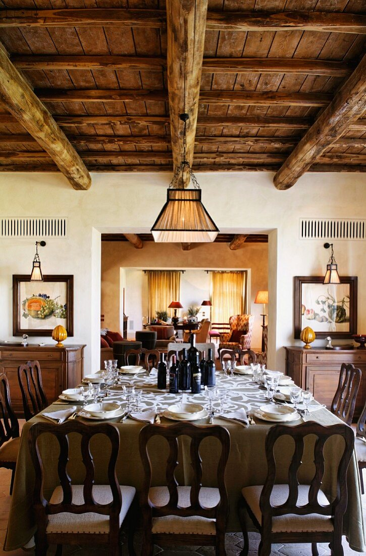 A dining room with a view into another room - a laid dining table with antique wooden chairs under a rustic wood beamed ceiling