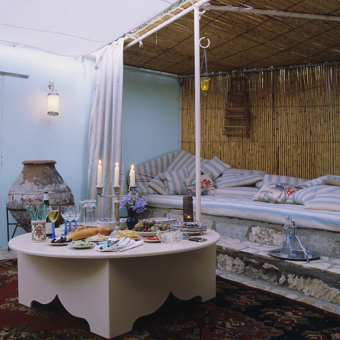 Mediterraner Abendessen mit Kerzenlicht vor Liegepolstern auf Steinpodest und Bambuswand
