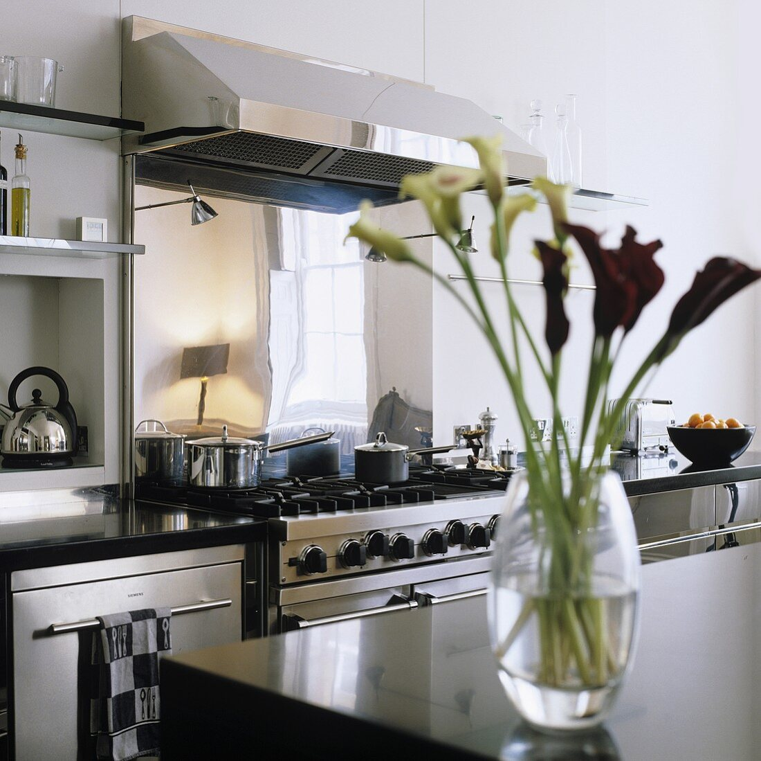 A stainless steel cooker with an extractor fan and a vase of lilies