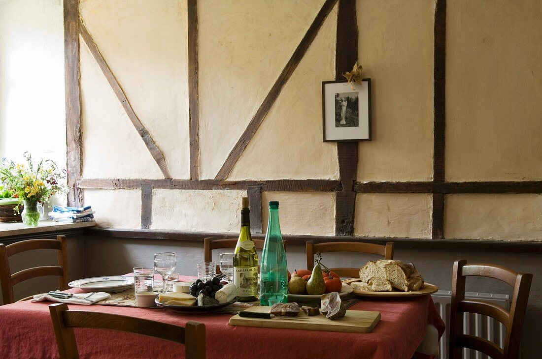 Supper in the dining room of a country house in front of a half-timbered wall