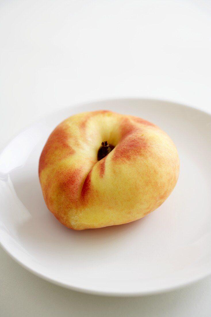 A Single Organic Saucer Peach on a White Plate