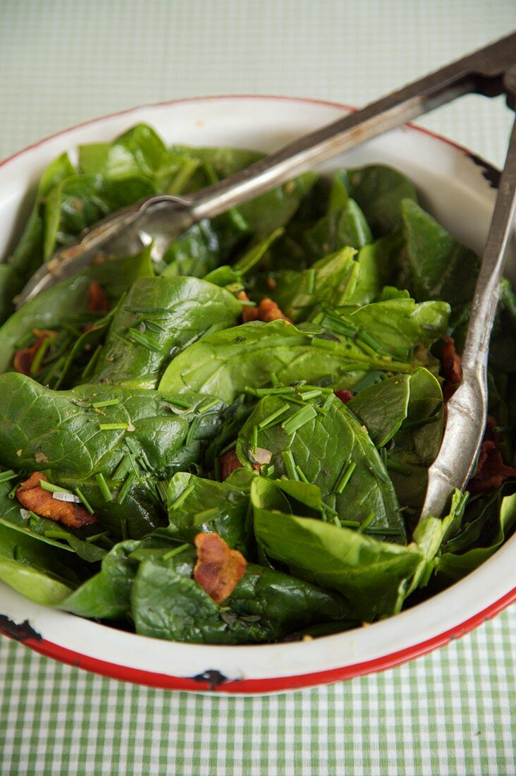 Tongs in a Serving Bowl of Spinach Salad with Bacon Dressing