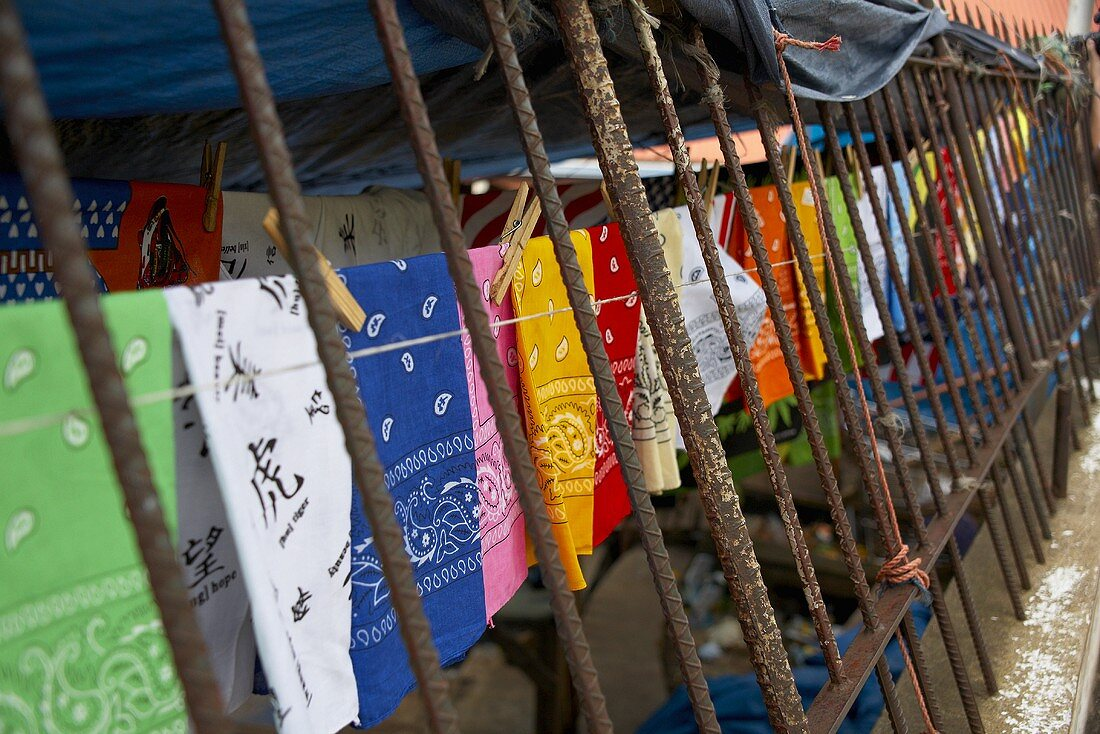 Colored Bandanas Hanging on a Clothes Line By an Iron Fence