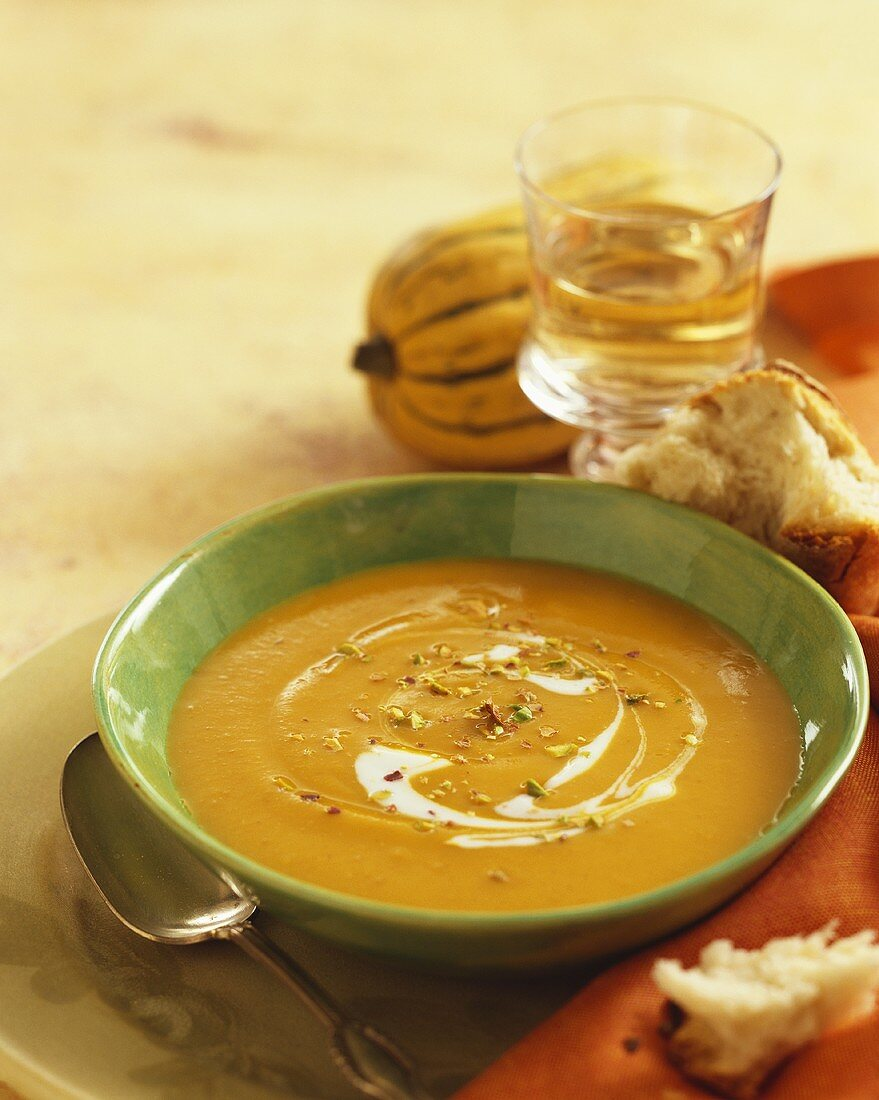 Bowl of Squash Soup, Spoon and Pieces of Crusty Bread