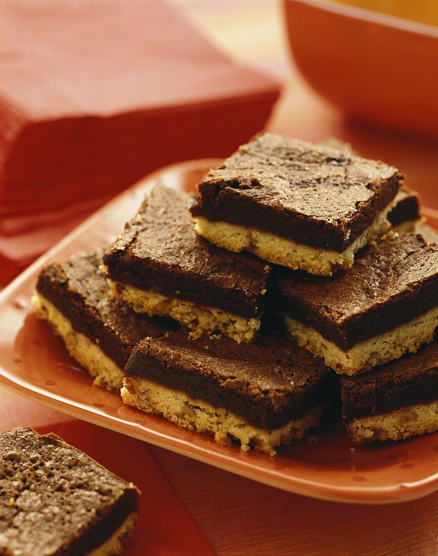 Brownie Pecan Shortbread Bars Stacked on an Orange Plate