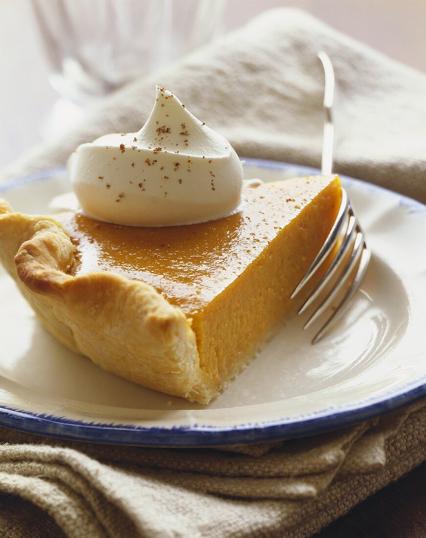 Slice of Pumpkin Pie with a Dollop of Whipped Cream, On a Plate with Fork