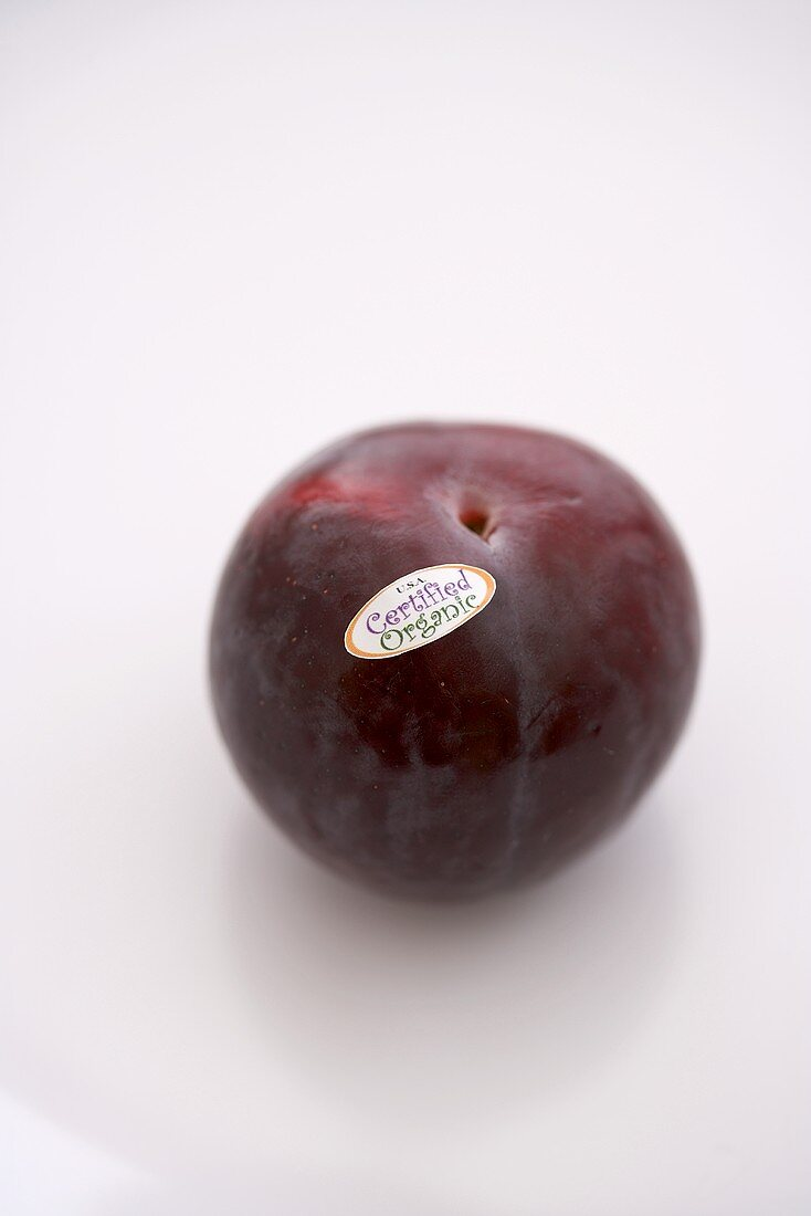 Organic Plum with Sticker on a White Background