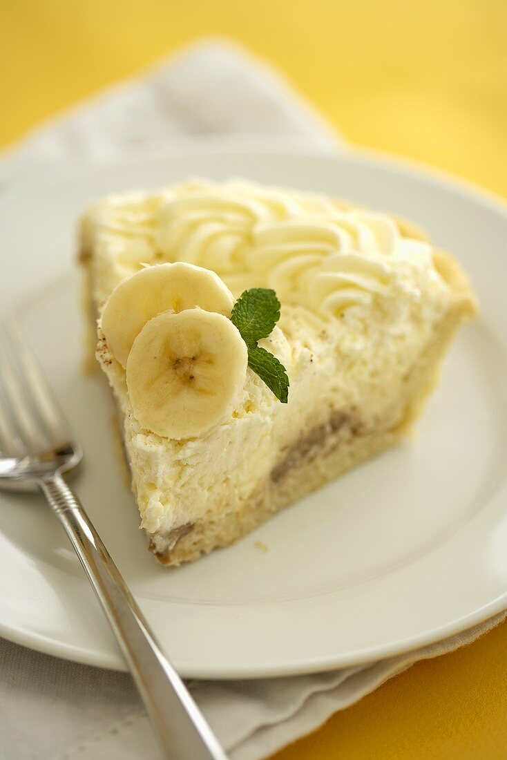 Slice of Banana Cream Pie on a White Plate with a Fork