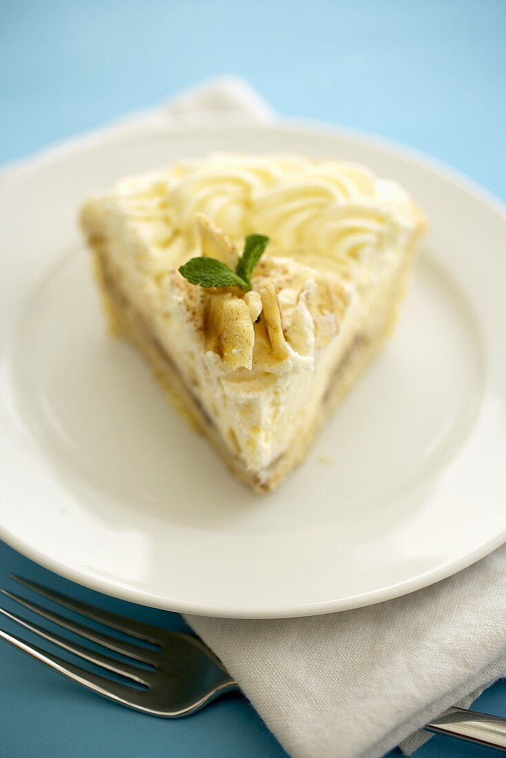 Slice of Banana Cream Pie on a White Plate; Blue Background