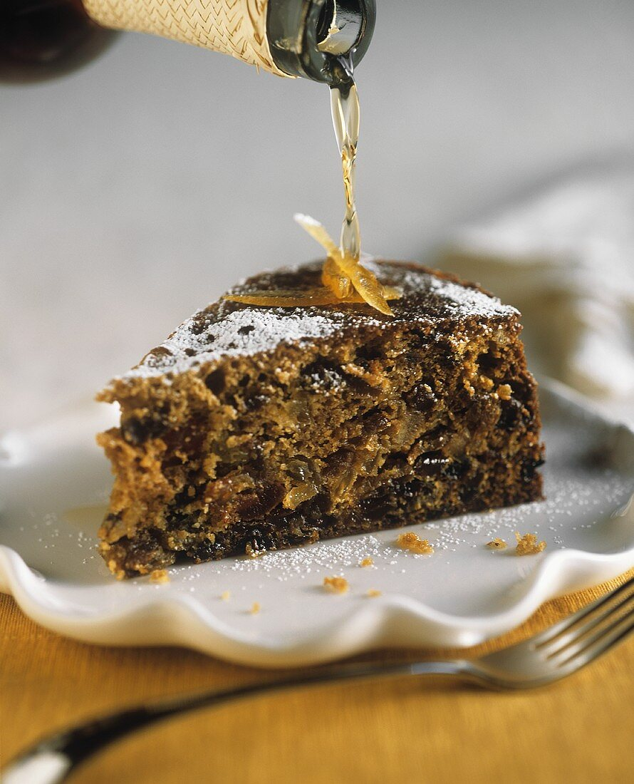 Pouring Brandy Over a Slice of Fruit Cake