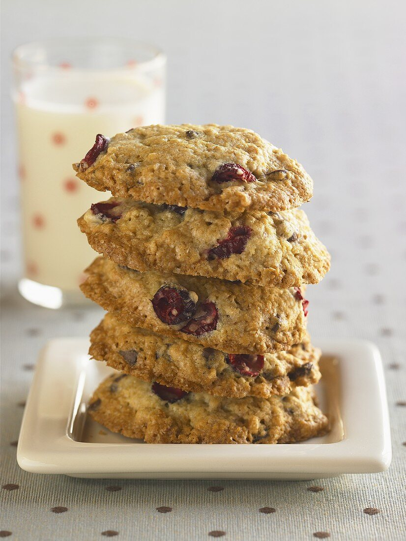 Oatmeal Cranberry Cookies Stacked on a Plate; Glass of Milk