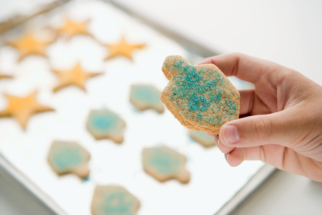 Hand Holding a Dreidel Sugar Cookie with Blue Sprinkles Over Baking Sheet