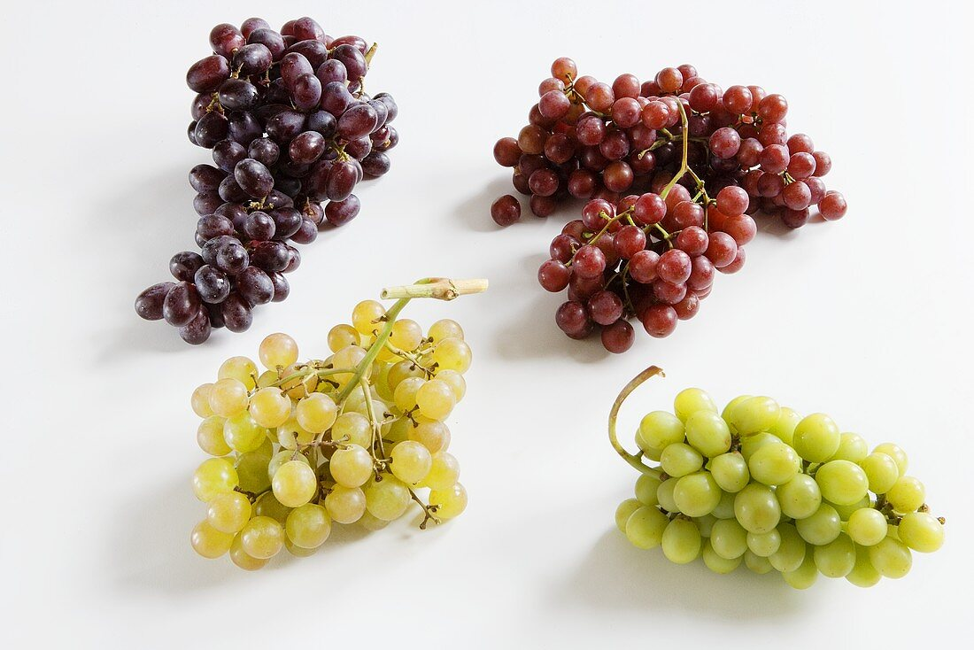 Four Bunches of Assorted Grapes on a White Background