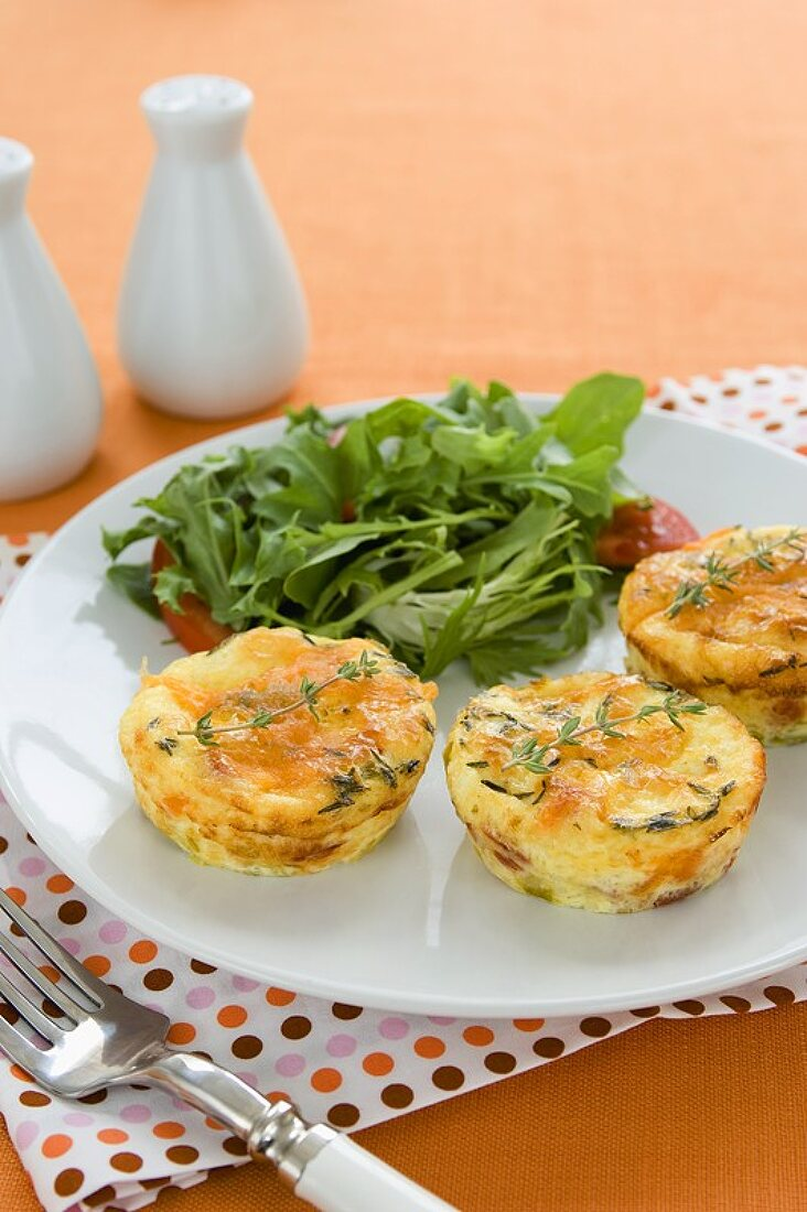 Three Crustless Mini Quiches on a Plate with a Side Salad