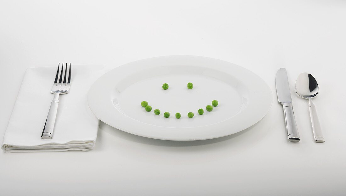 Place Setting with Peas Forming a Smiley Face on White Plate