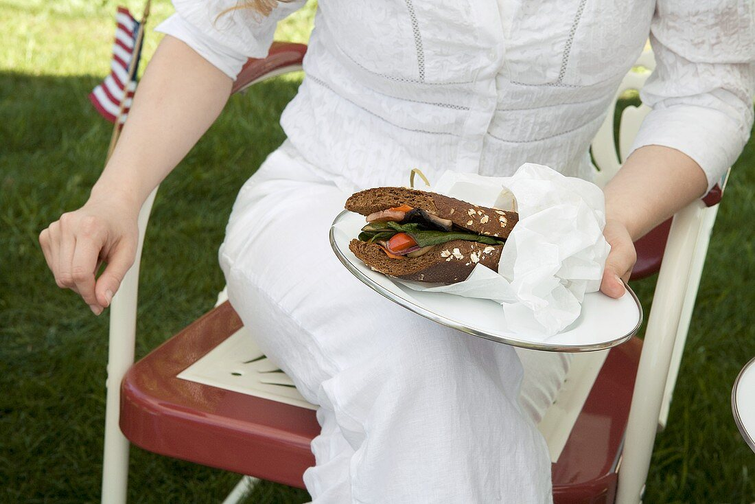 Woman Holding Partially Wrapped Sandwich on a Plate on Lap