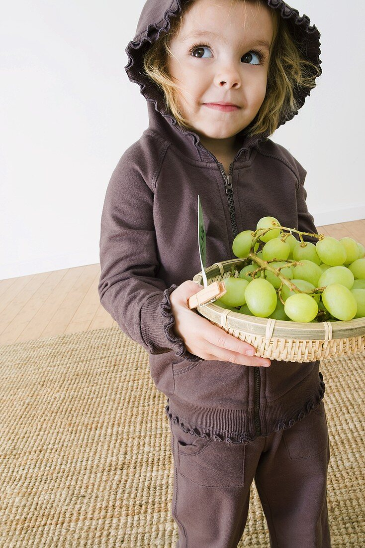 Little Girl Holding a Basket of Grapes