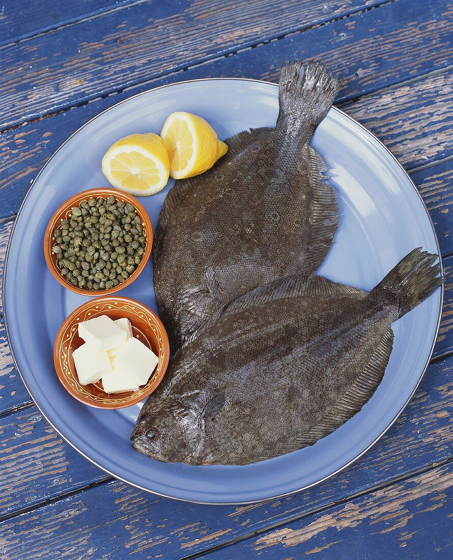 Fresh Flounder on Plate with Butter, Lemons and Capers