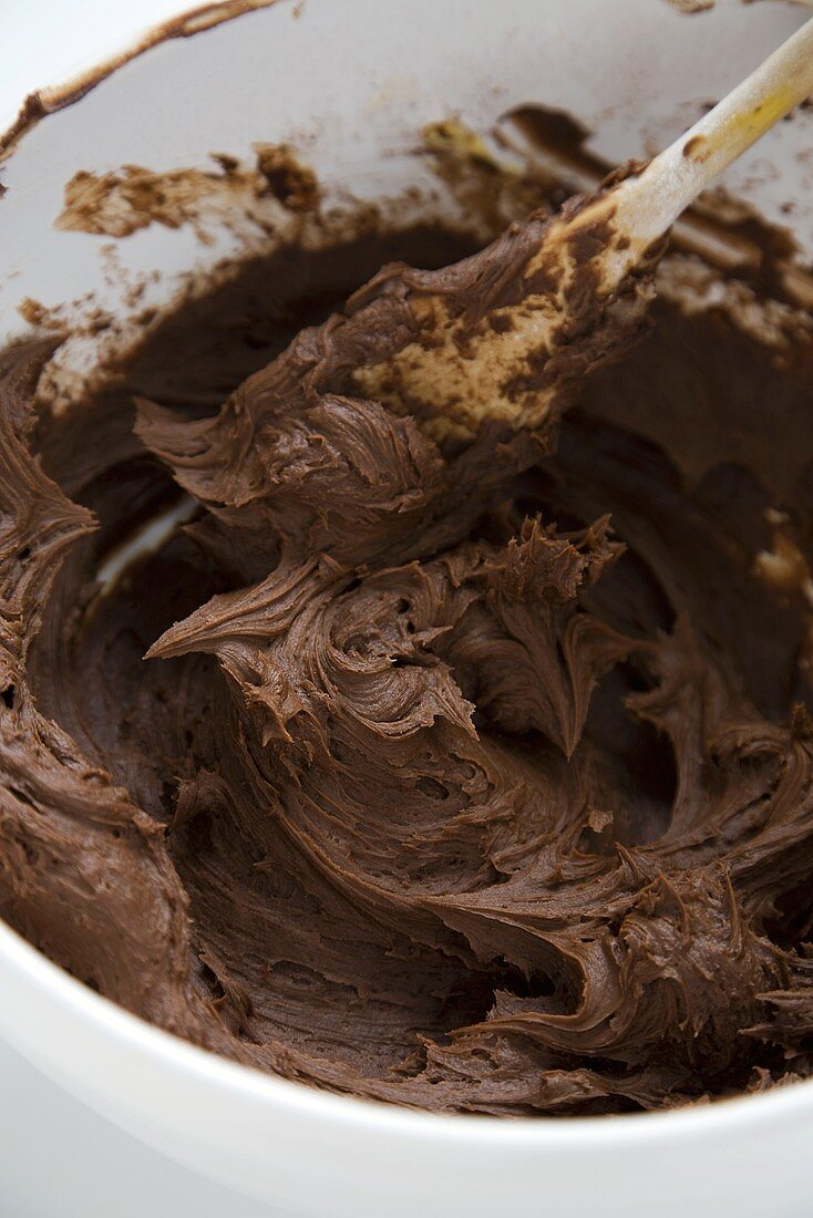 Chocolate Icing in a Mixing Bowl with a Wooden Spoon