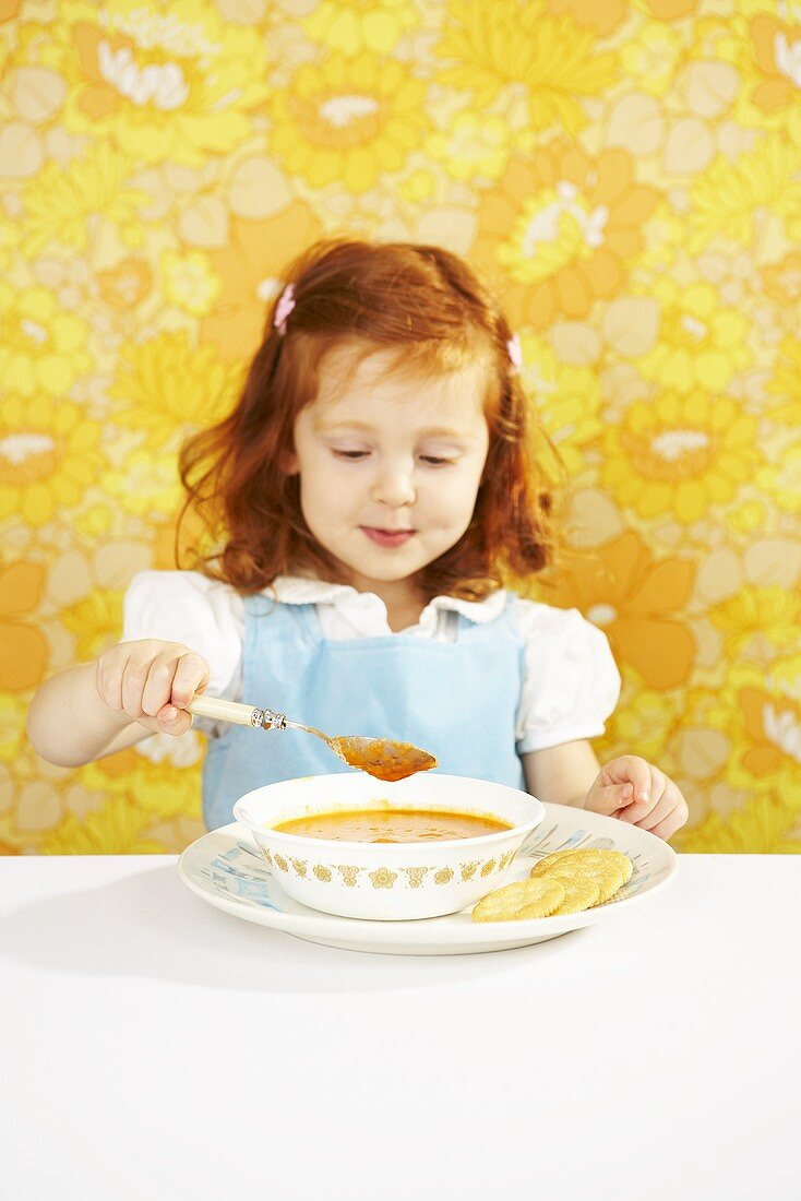 Red Headed Girl Sitting at Table with a Bowl of Tomato Soup